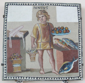 A boy holding a platter of fruits and a bucket of crab(?) in a kitchen with fish and squid, on the June panel from a mosaic depicting the months (3rd century) CC Commons - creator Sailko